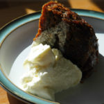 christmas pudding in a blue dish, with cream on top